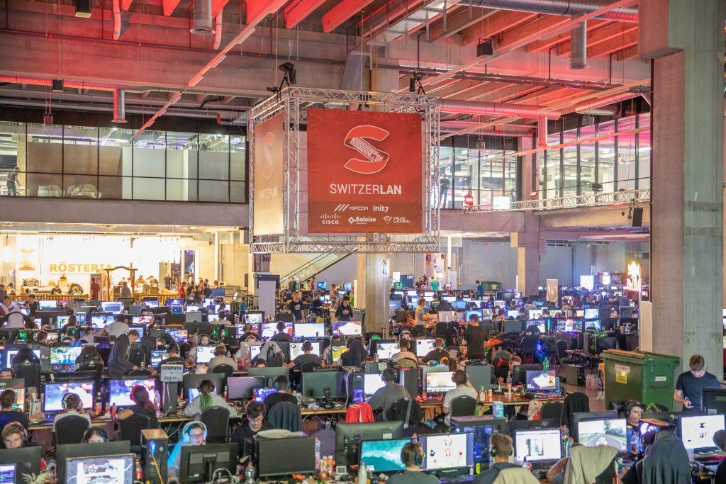 Bild der SwitzerLAN 2018 Mehrere Reihen an Besuchern an ihren PCs Ein grosses Logo prangt in der Mitte des Raumes