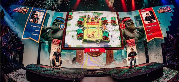 Foto eines Clash Royale Finales. Zusehen ist eine Bühne in blauer und roter Farbe. Ein grosser Bildschirm in der Mitte zeigt das Spielgeschehen. Die Spieler sitzen an jeder Seite in einem grossen Sessel.