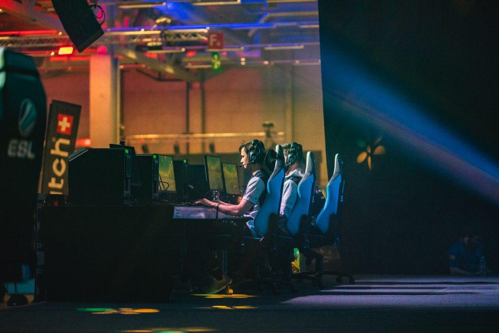 Gamer sitzen an einem Pult und spielen Videospiele.