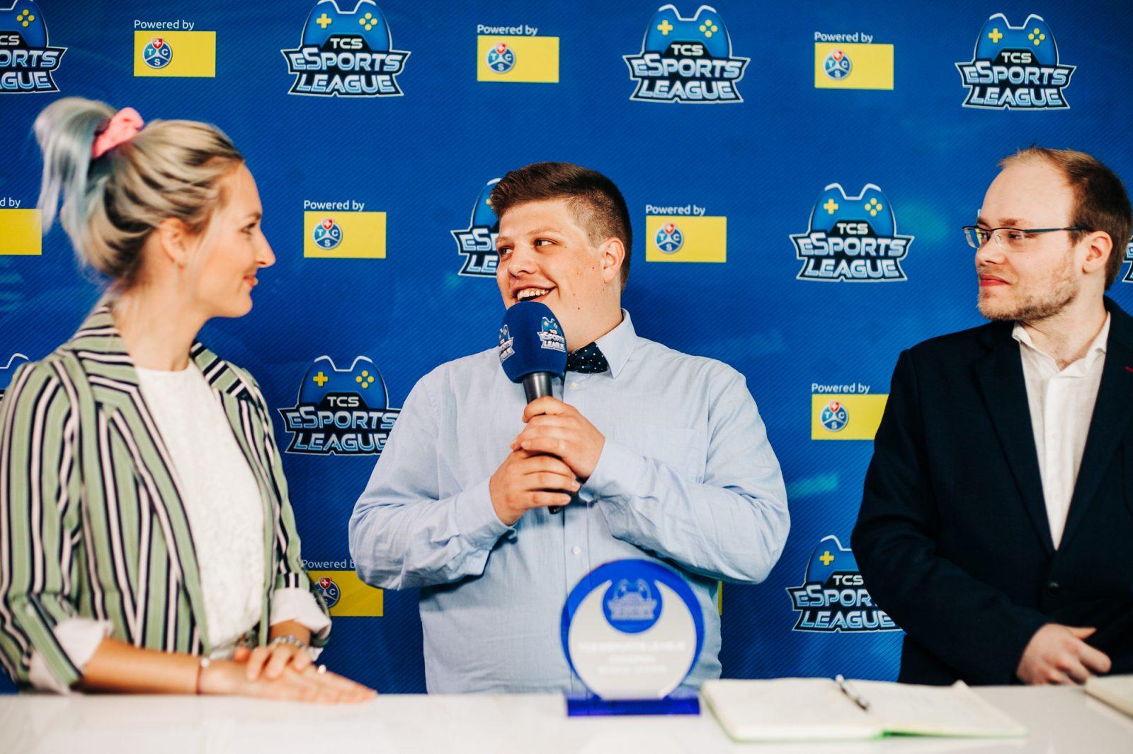 Eine Frau und zwei Männer sprechen mit Mikrofon miteinander. Vor ihnen steht ein Pokal.