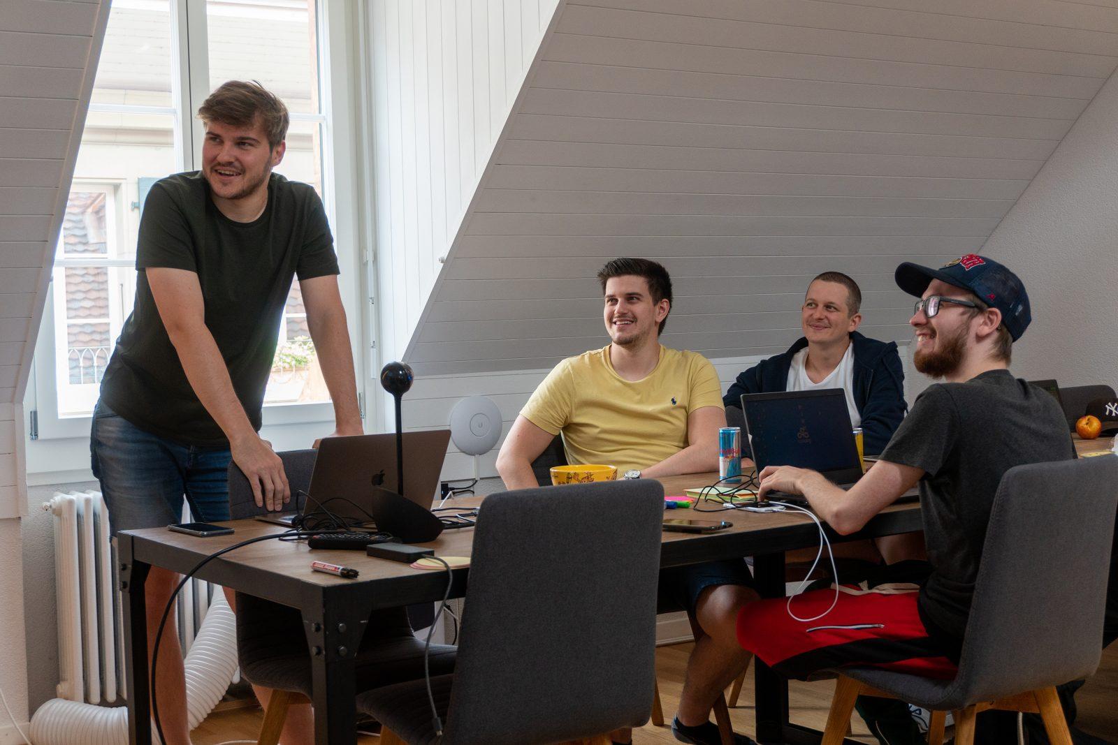 Vier lachende Männer in einem Meeting.