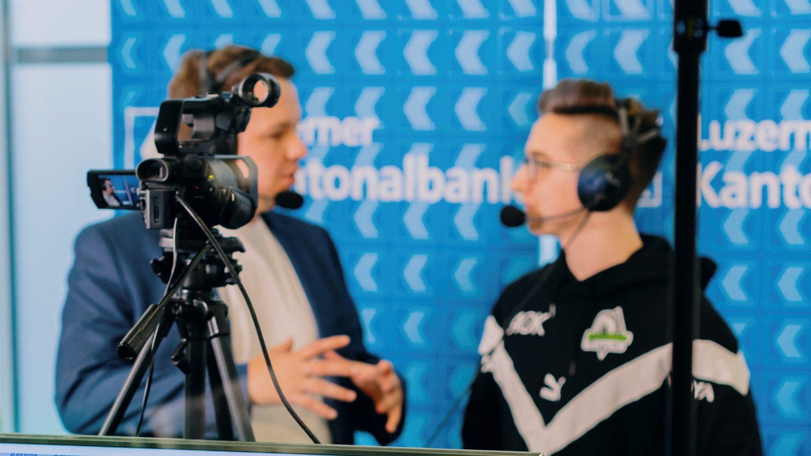Zwei Männer mit Headsets moderieren vor einer Kamera.