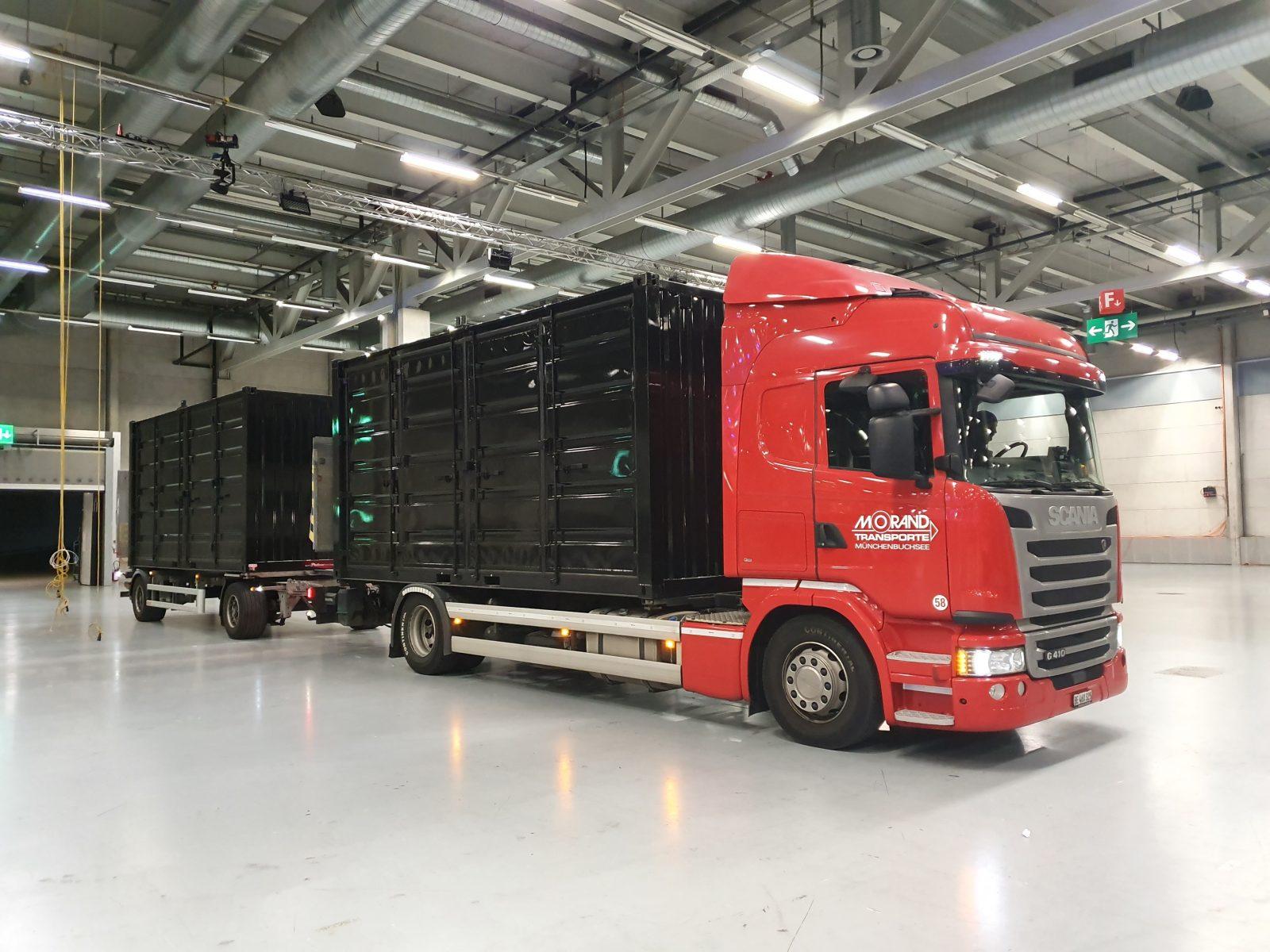 Roter Lastwagen mit schwarzem Container steht in der Messehalle Bernexpo.
